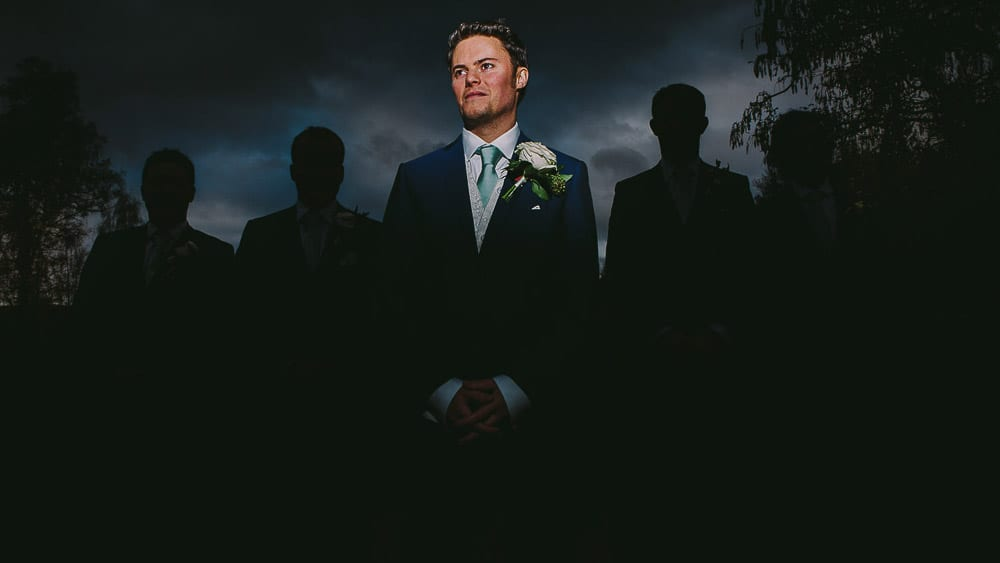 A groom lit up stands in front of the silhouettes of his groomsmen