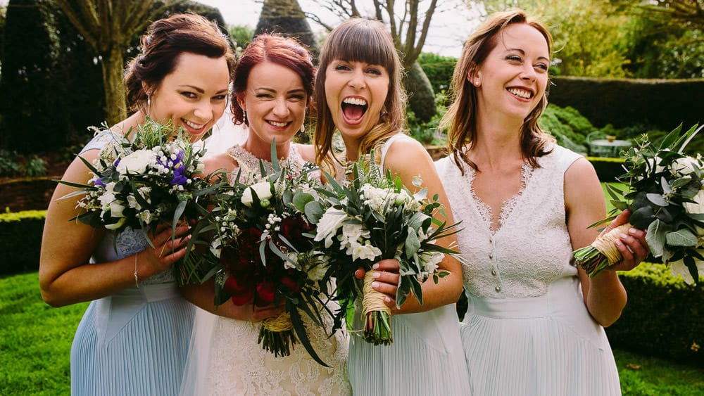 A bride and bridesmaids laughing at Dewsall Court