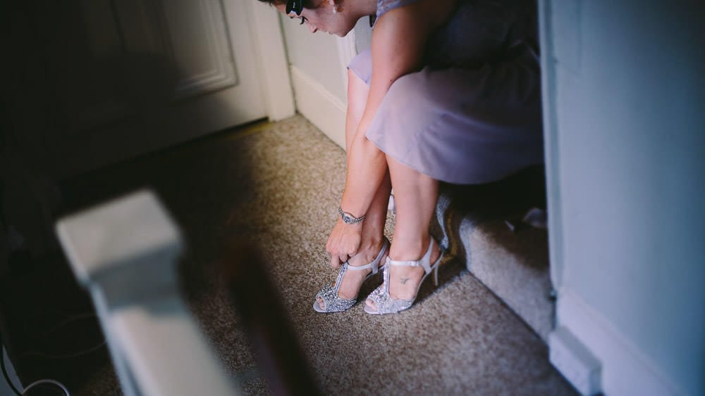 A bridesmaid tying her shoes at Grittleton House