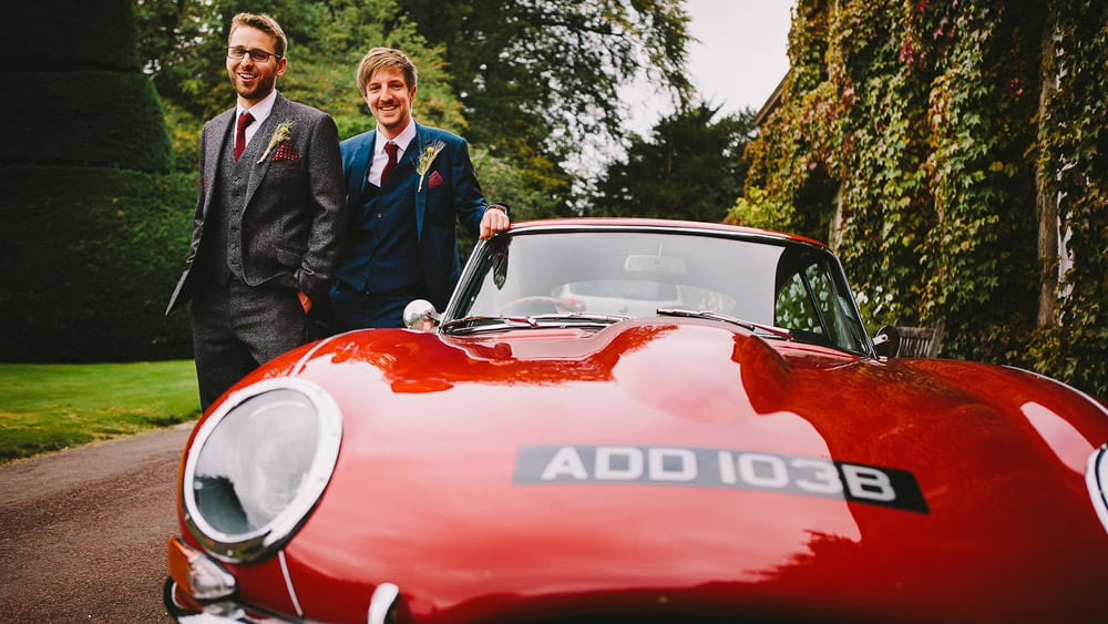 Groom and his best man with red e-type Jaguar