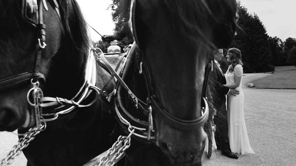 Black and white image of bride and groom with horse and carriage at Grittleton