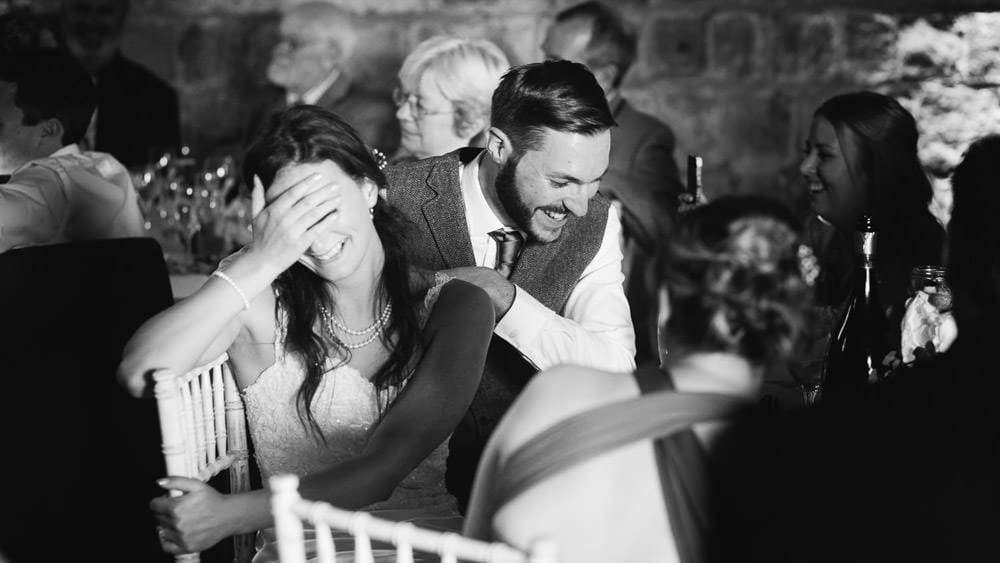 Bride and groom laughing at speeches at Wick Bottom Barn
