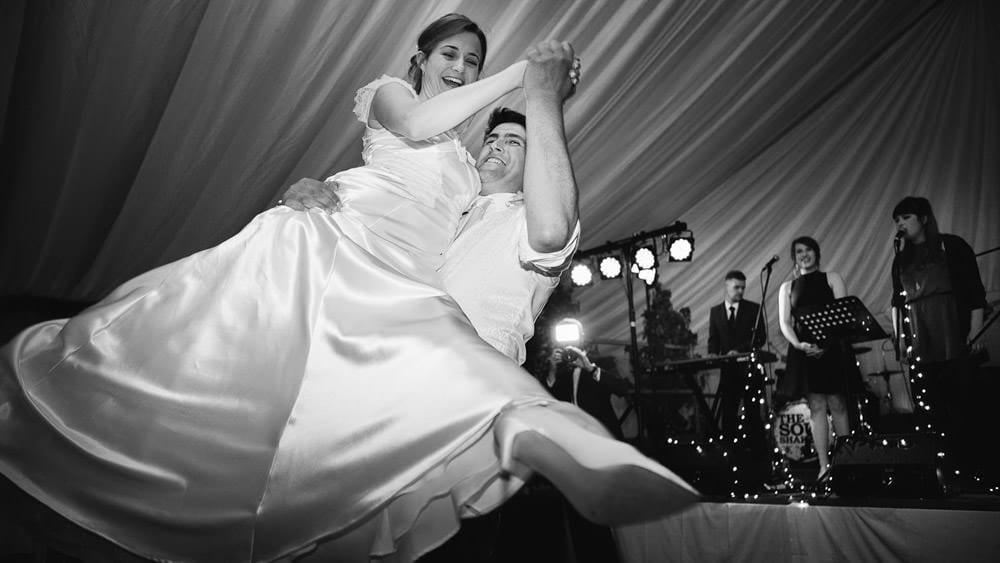 Black and white image of bride and grooms first dance in marquee wedding