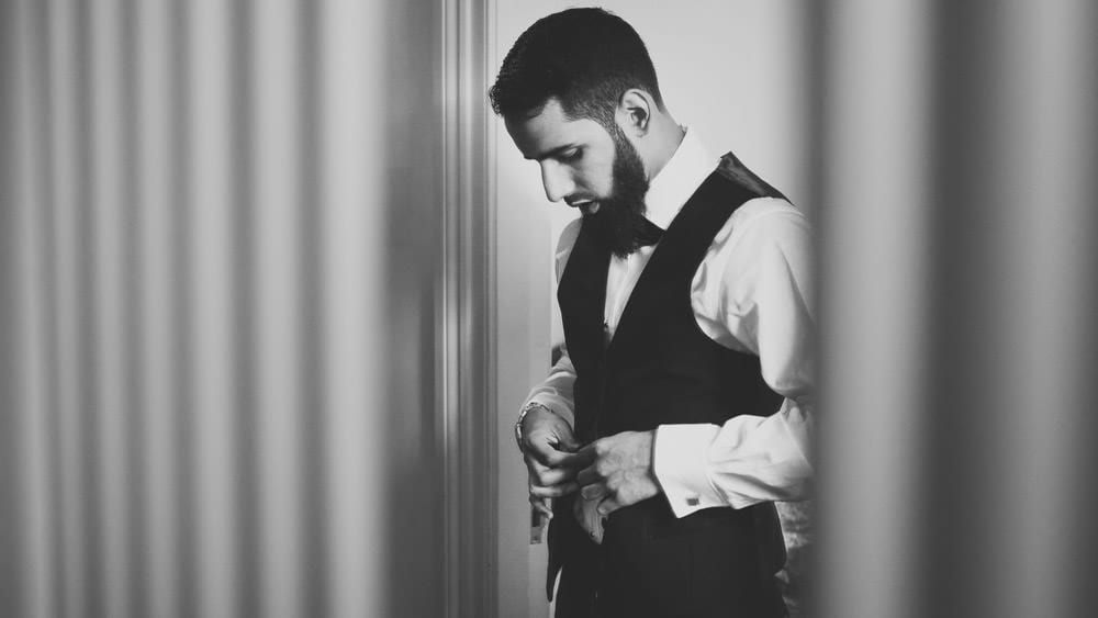 Groom buttoning up his waistcoat for muslim wedding
