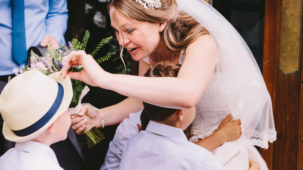 Bride playing with young guests hat outside church