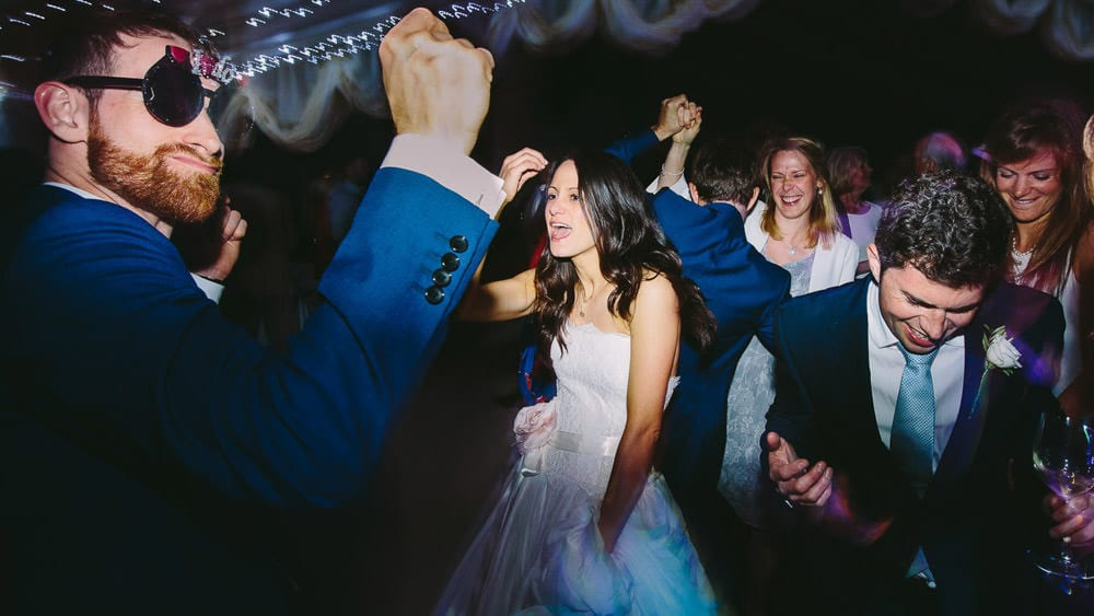 A bride and her guests dancing wildly