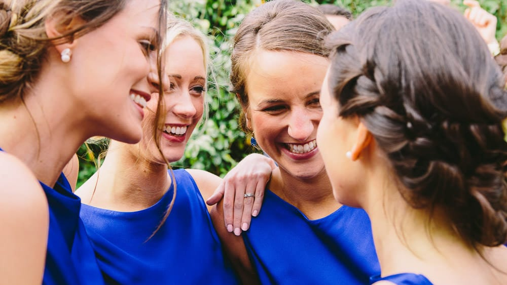 Bridesmaids all having a hug and laughing together