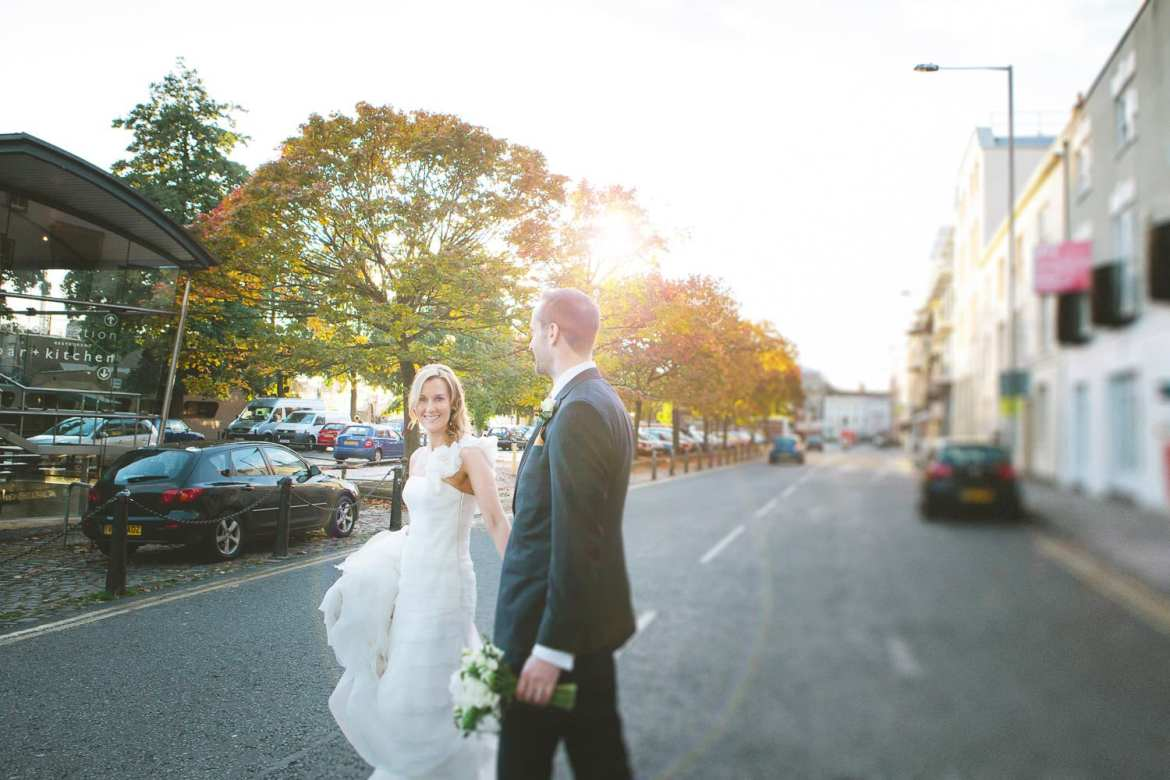 The bride and groom walk across the road towards riverstation