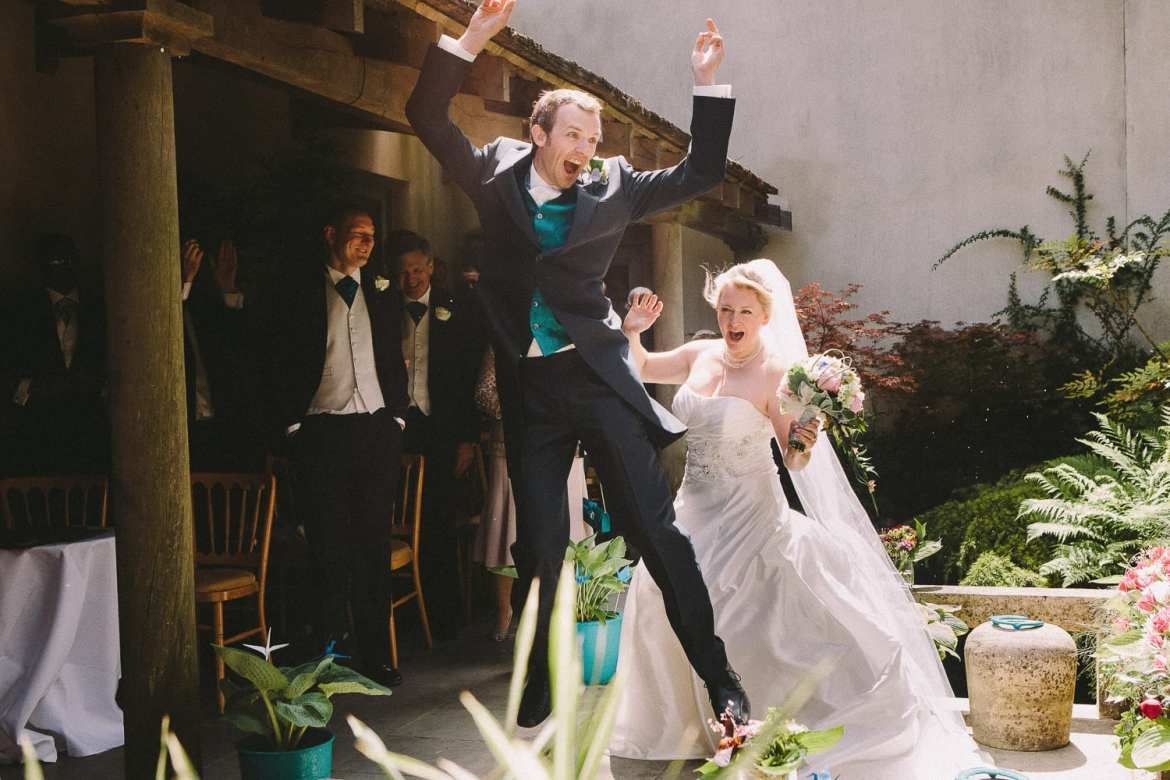 The bride and groom jump for joy