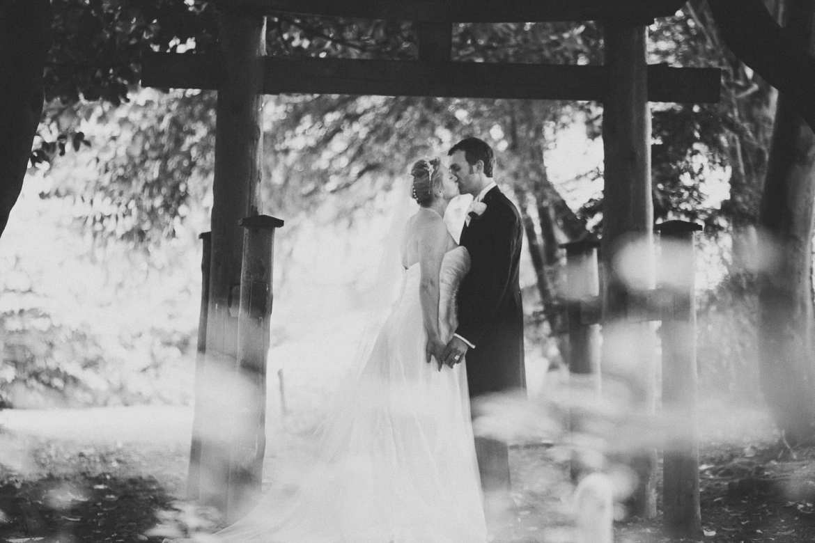 The bride and groom kiss in the woods