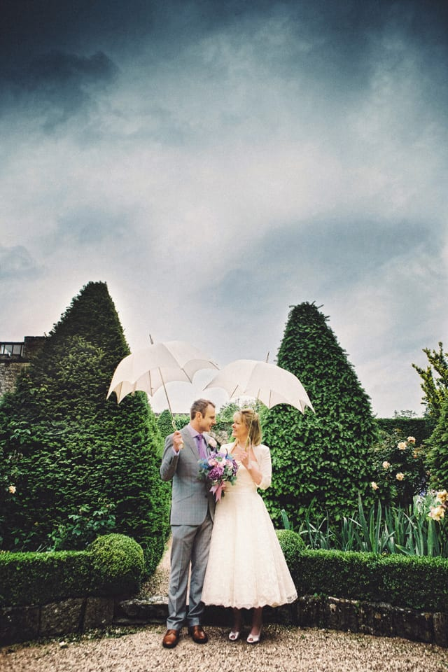 bride and groom hold umbrellas at abbey house gardens