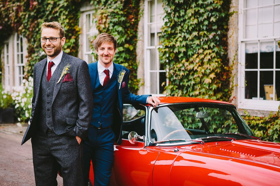 groom and best man pose by car
