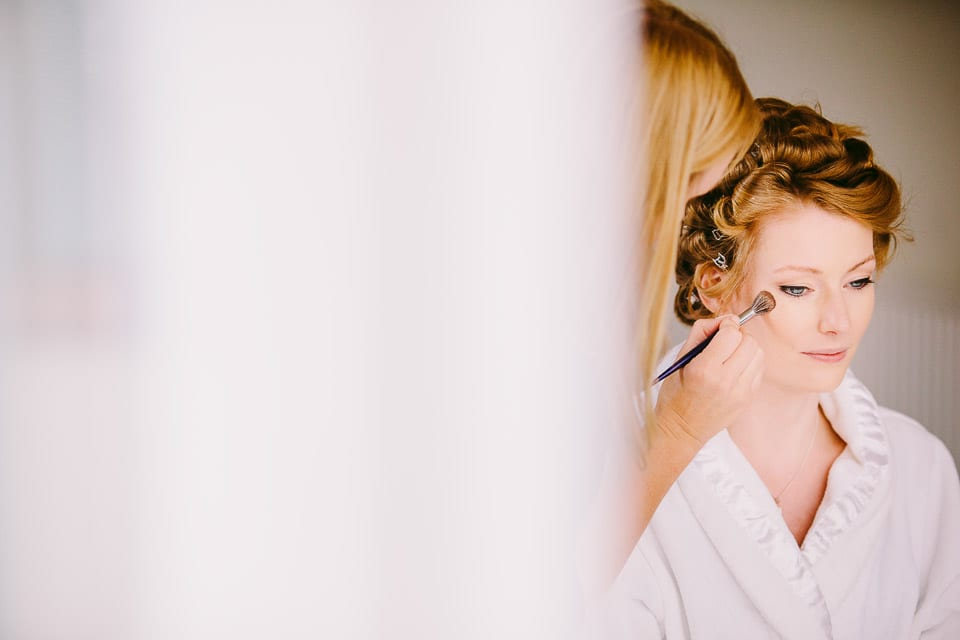 The bride sits while the make up artist applies foundation