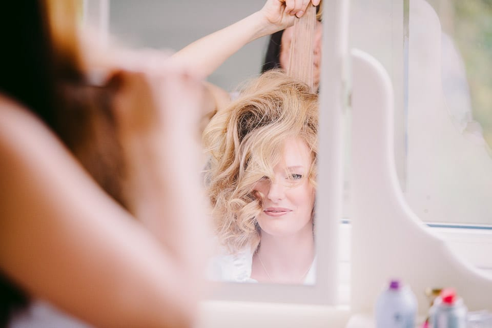 The bride having her hair done in the mirror