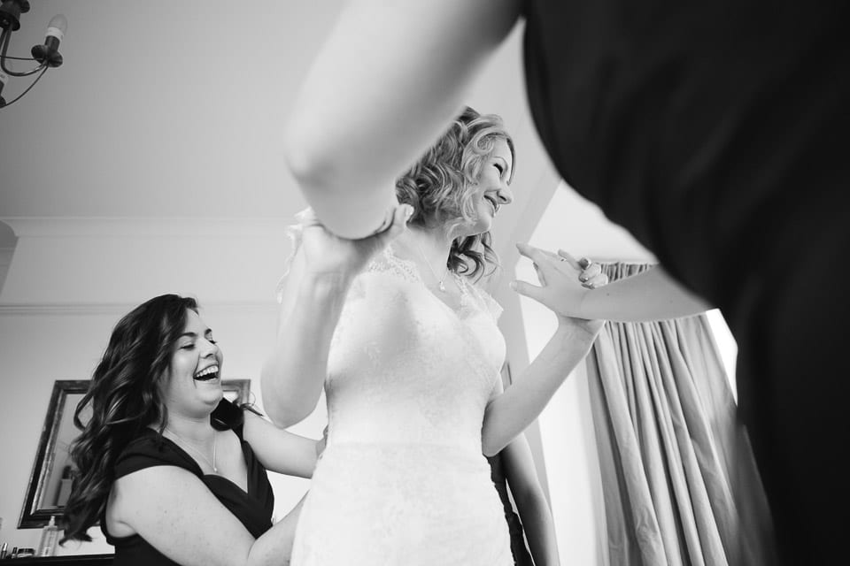 The bridesmaids are laughing and helping the bride into her dress