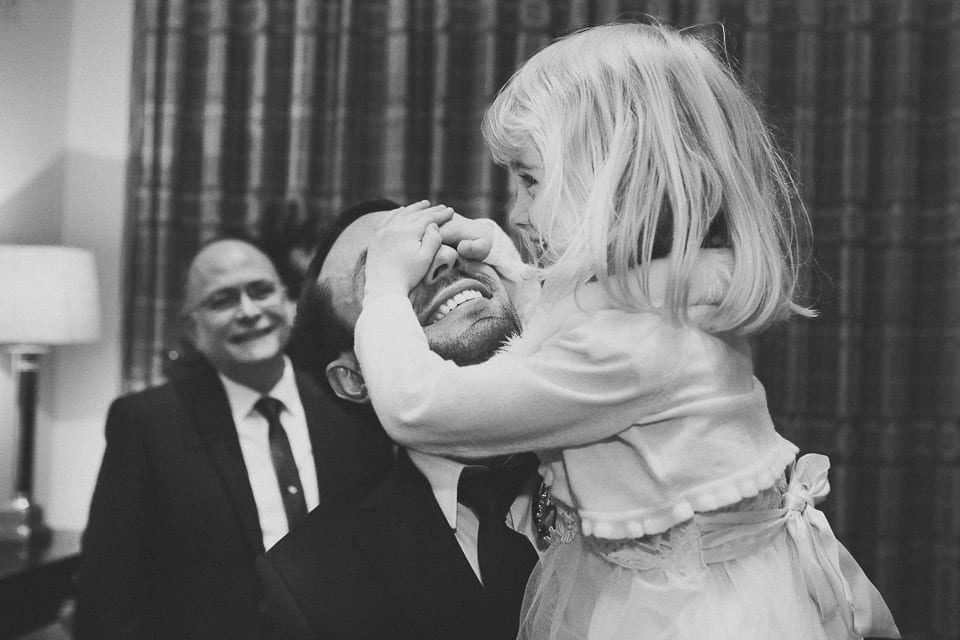 Laughing child hides her dad's face