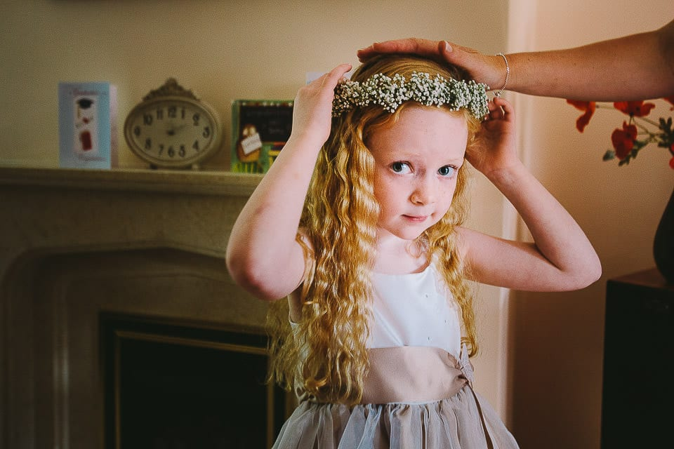 Flower girl playing with her headdress at home