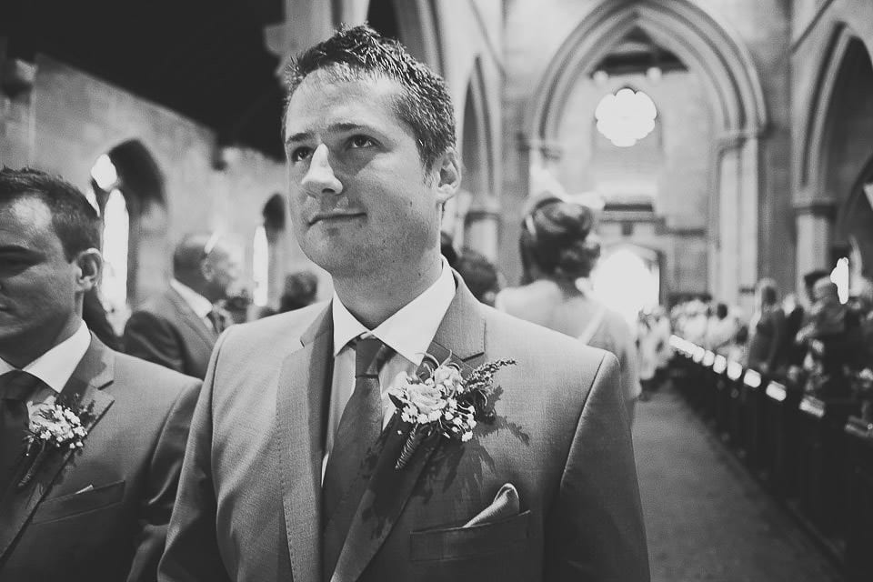 Groom waiting at the front of the church for his bride to enter