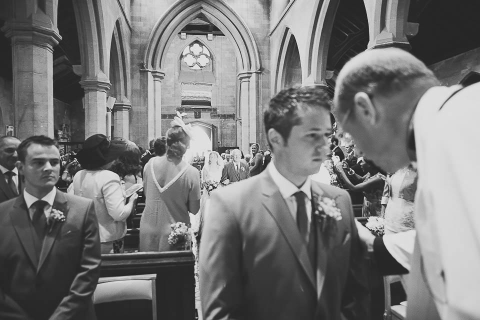 Vicar speaking to the groom in the church