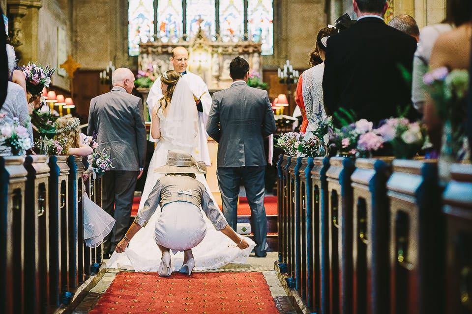 Mother of the bride arranges her dress and veil in church