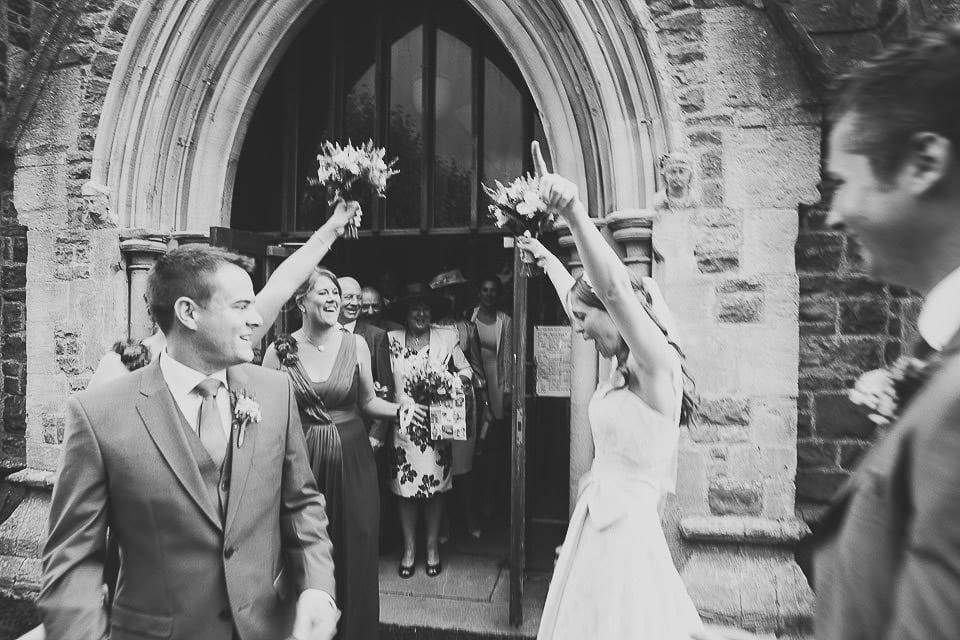 Bride waving her arms in the air outside the church
