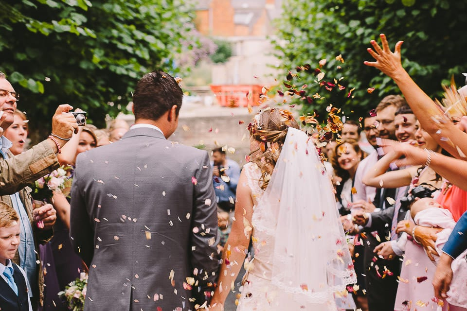 Rear shot of bride and groom walking through confetti tunnel
