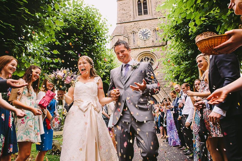 Bride and groom walking through confetti tunnel outside church