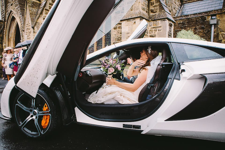 Bride and groom get into McLaren to drive to Abbey House Gardens