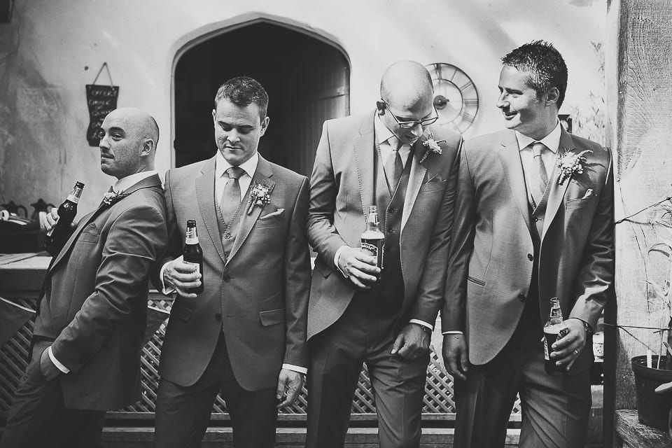 Groom and his groomsmen leaning against each other at the bar at Abbey House Gardens