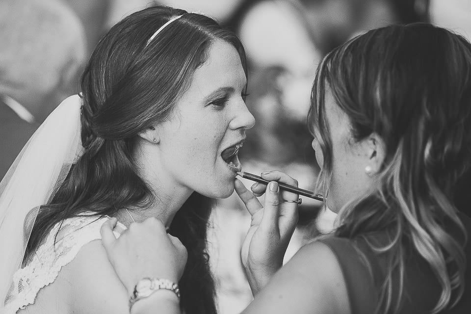 Bride having her lipstick touched up at Abbey House Gardens