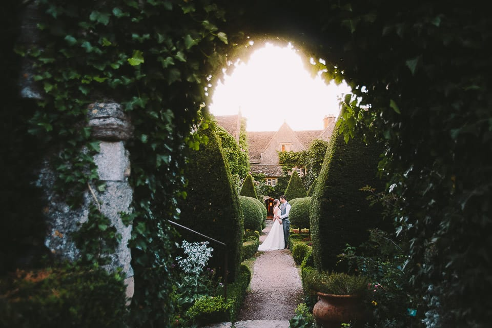 Full length portrait of bride and groom through archway at Abbey House Gardens