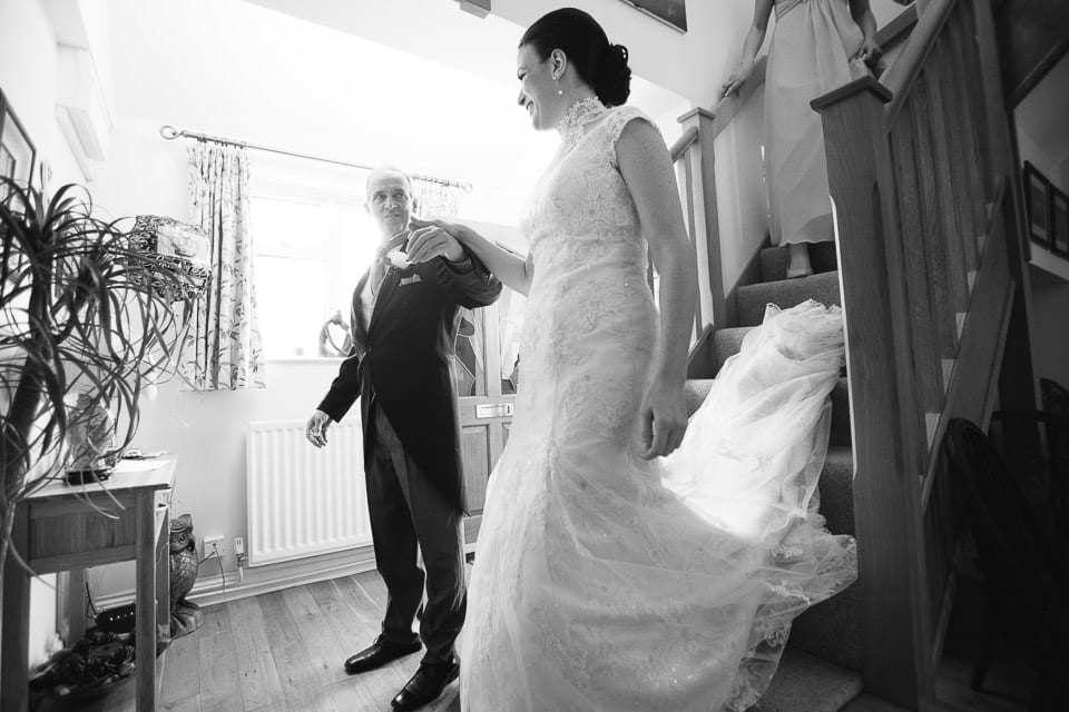 Black and white image of bride coming down stairs