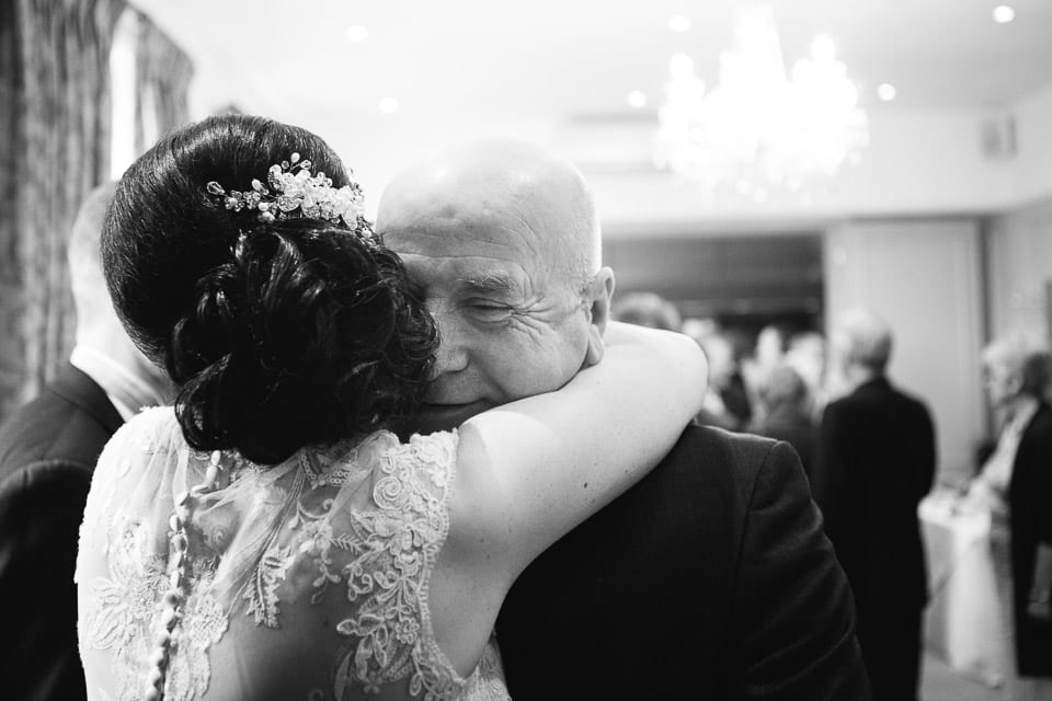 Black and white image of bride hugging guest
