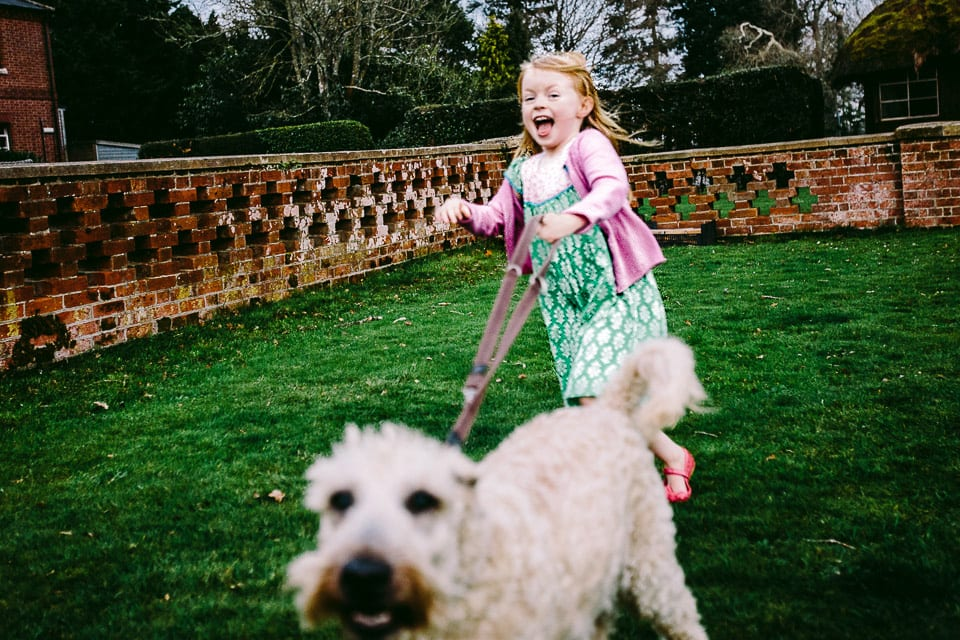 young girl running with dog on lead