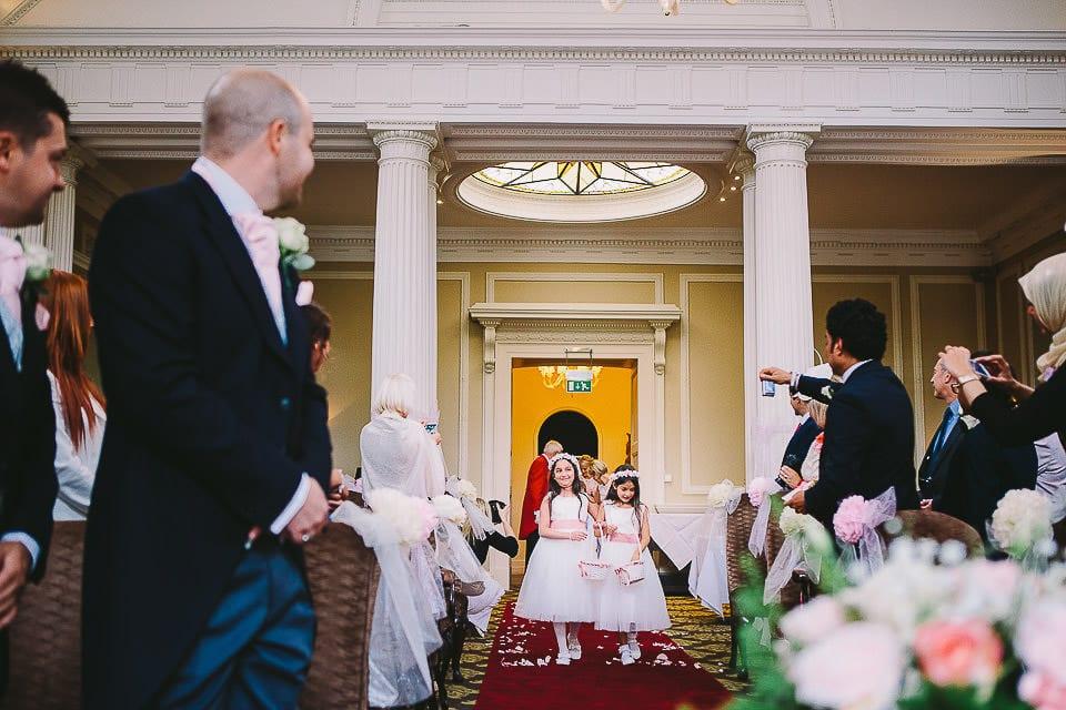 Young bridesmaids walking up the aisle at Bath Spa Hotel