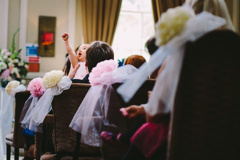 Young baby waving her arms in the air during the ceremony at Bath Spa Hotel