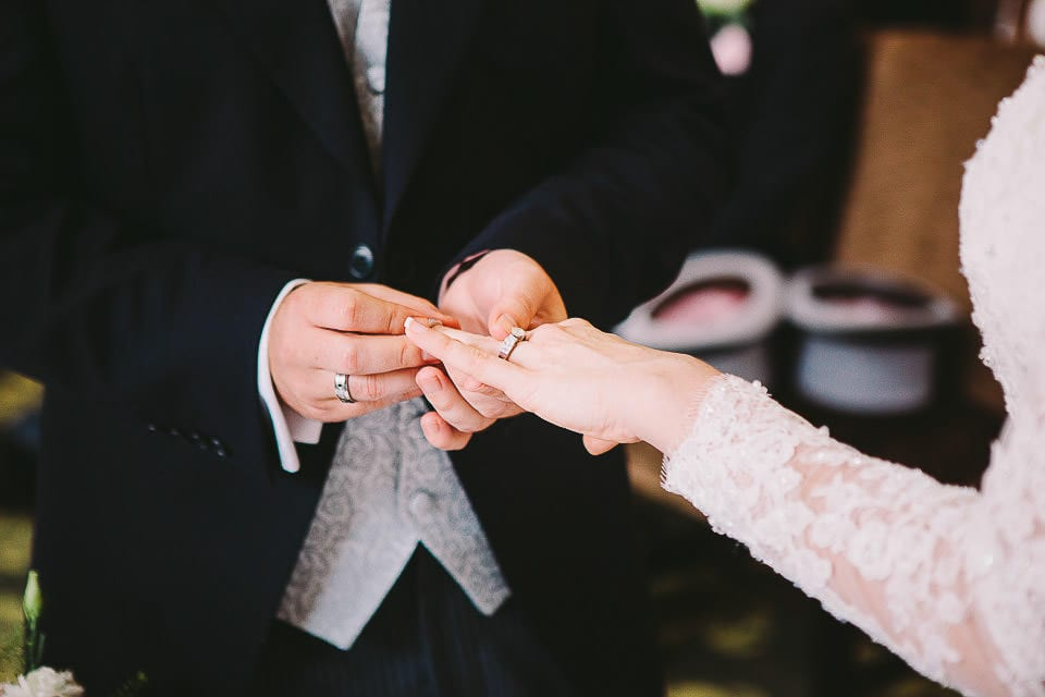 Groom placing wedding ring on brides finger at Bath Spa Hotel