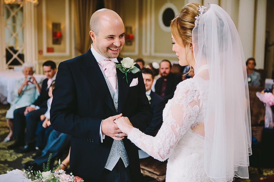 Bride and groom exchanging wedding rings at Bath Spa Hotel