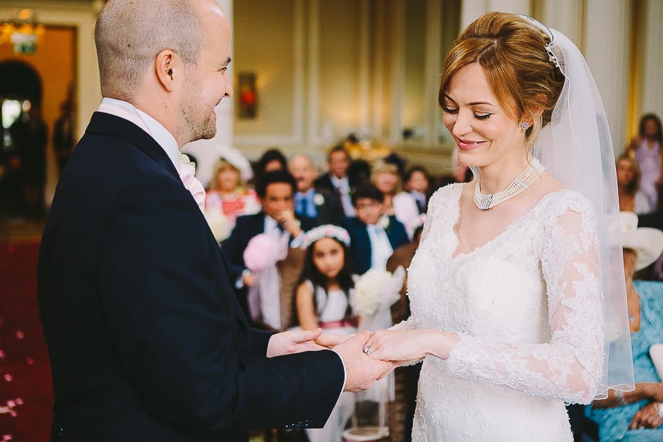 Groom places the wedding ring on his brides finger at Bath Spa Hotel