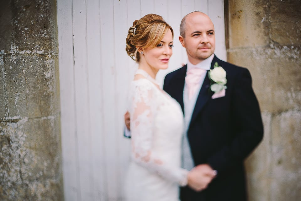 Portrait of bride and groom by pillars at Bath Spa Hotel