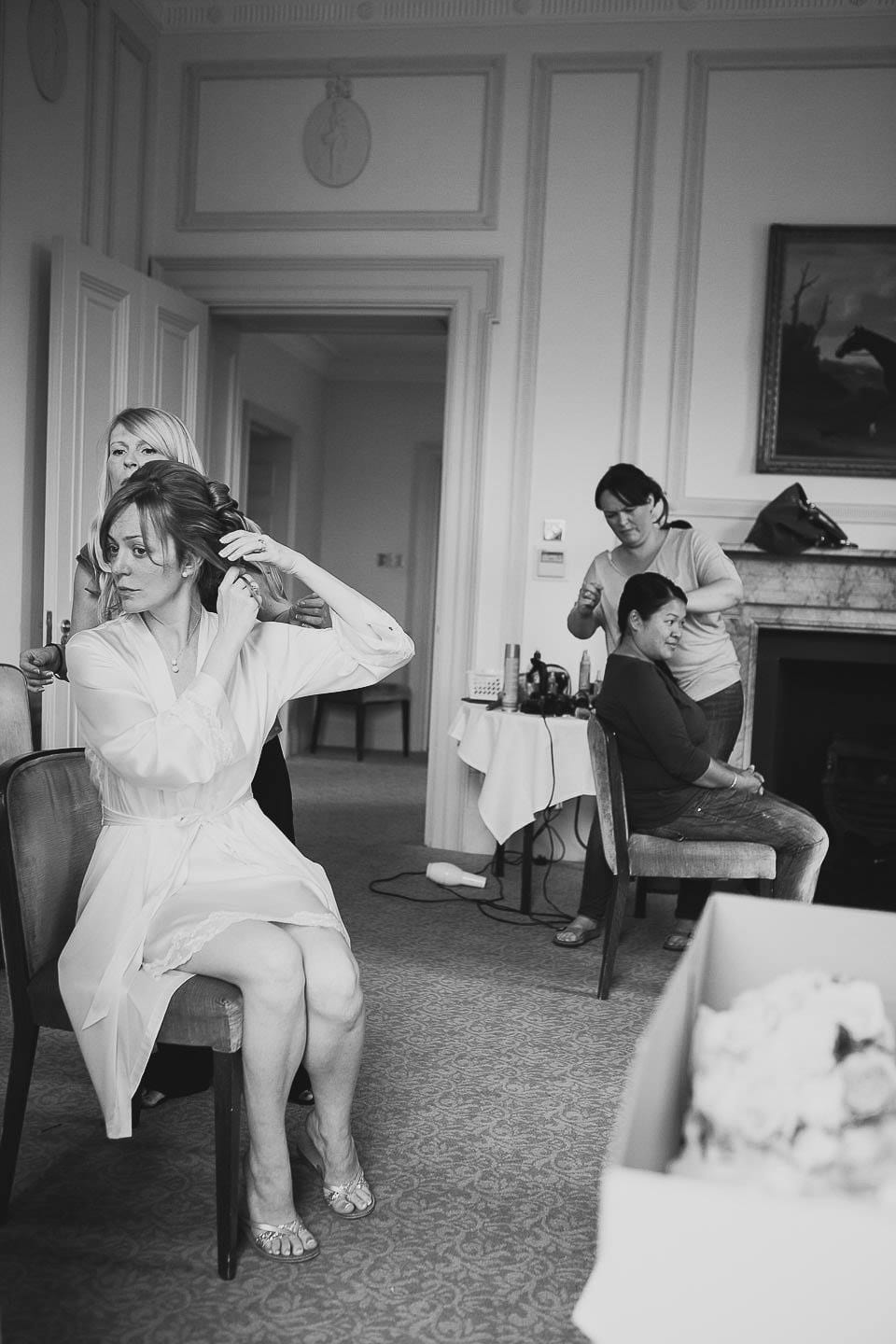 Black and white image of bride having her hair done at Bath Spa Hotel