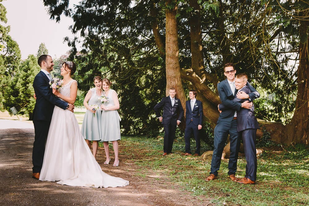 Bride and groom with bridesmaids and groomsmen under the trees at Grittleton House