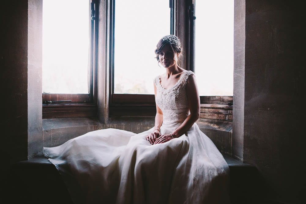 Bride sitting in the window above the grand staircase at Grittleton House