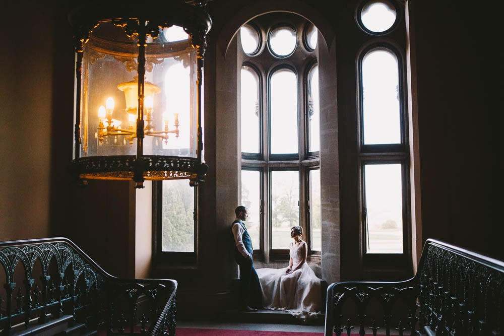 Portrait of bride and groom in the window above the grand staircase