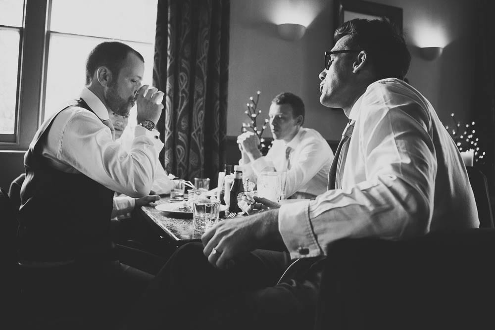 Black and white image of groom and his groomsmen in the Somerford Arms