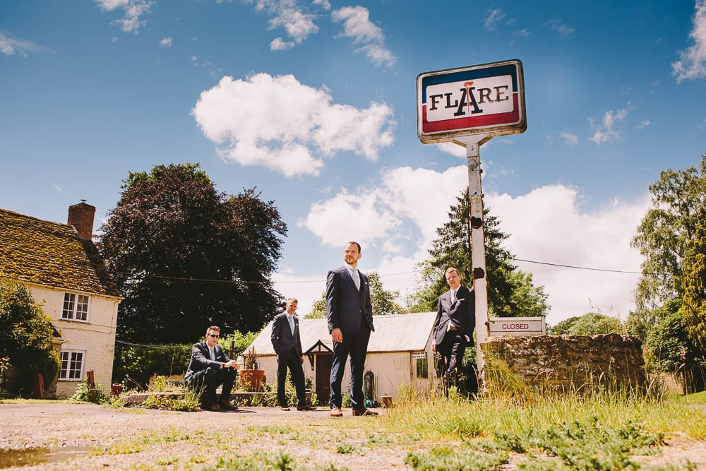 Groom and his groomsmen outside a disused garage in Little Somerford