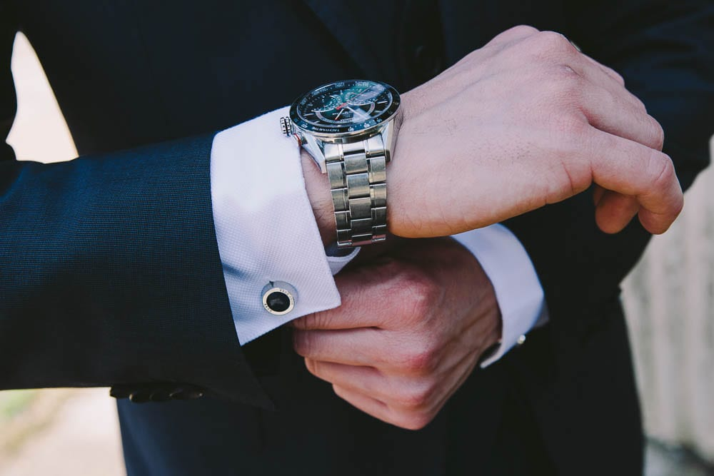 Close up image of grooms watch and cufflinks