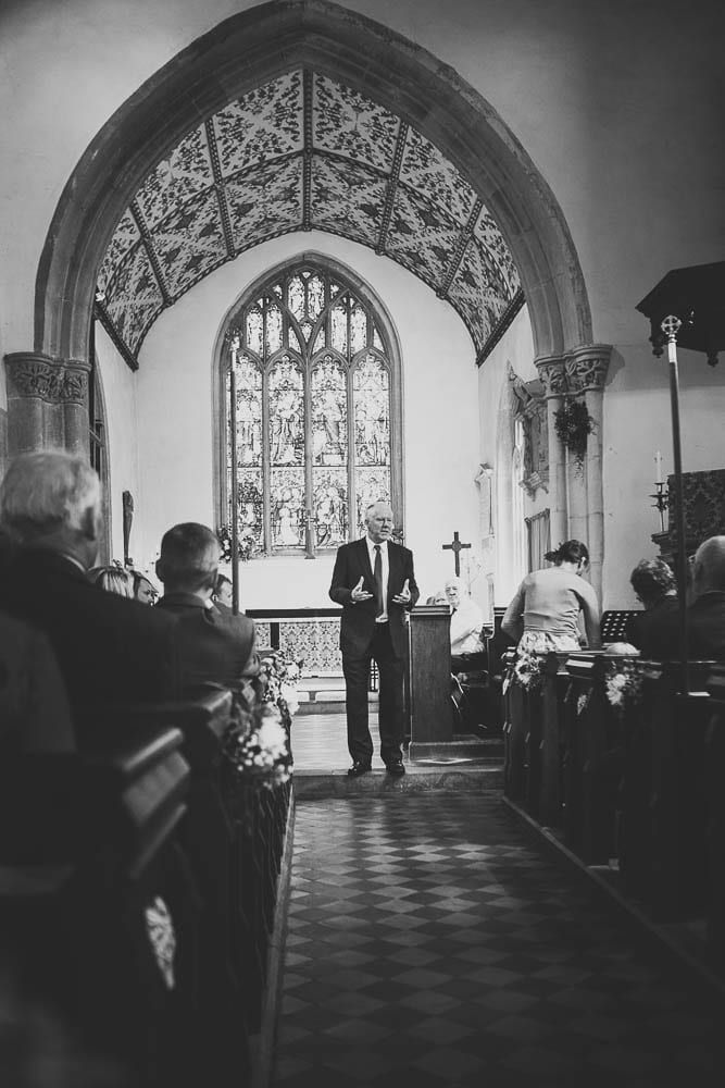 Black and white image of guests inside Great Somerford Church