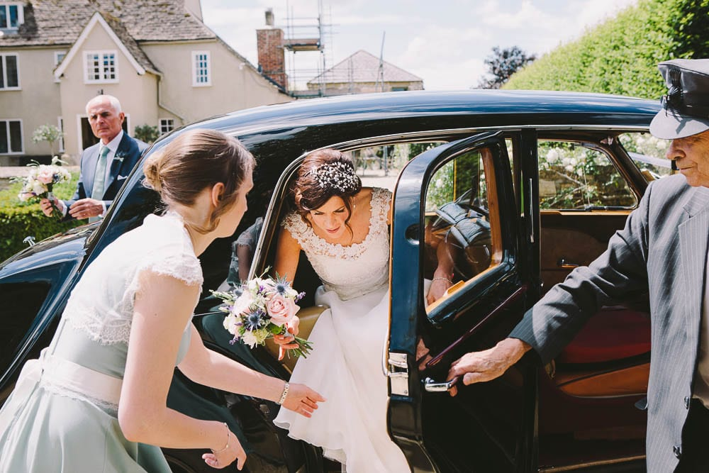 Bride getting out of the wedding car outside Great Somerford Church