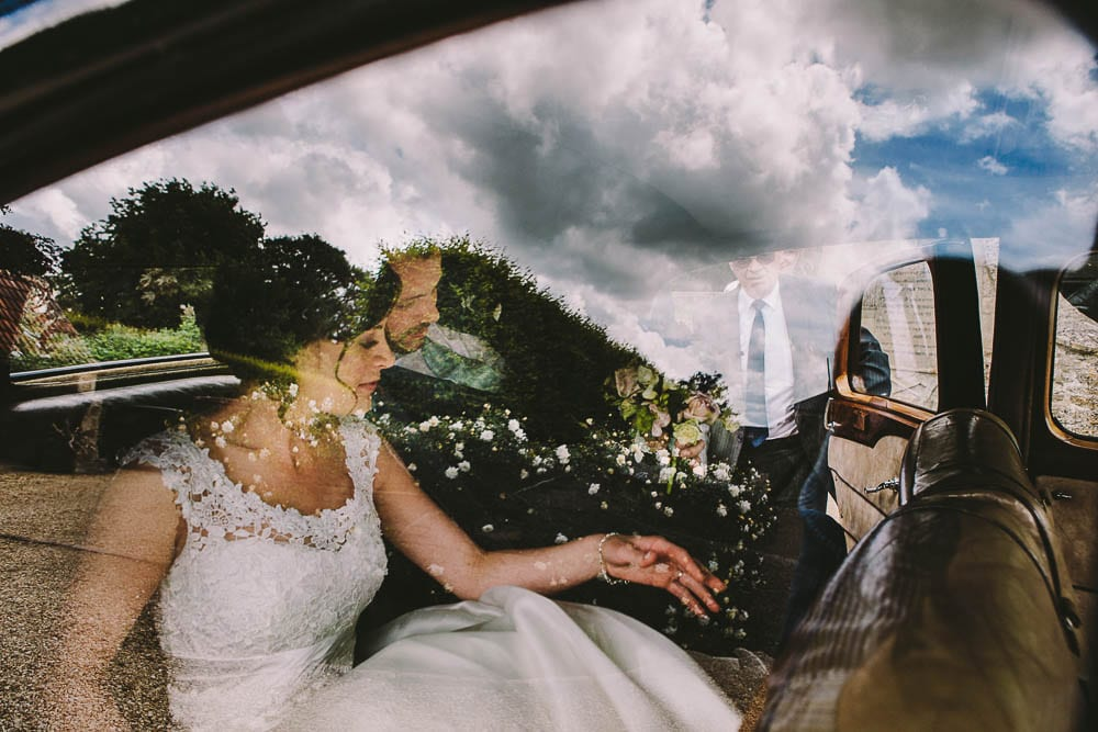 Bride and groom in the wedding car departing for Grittleton House